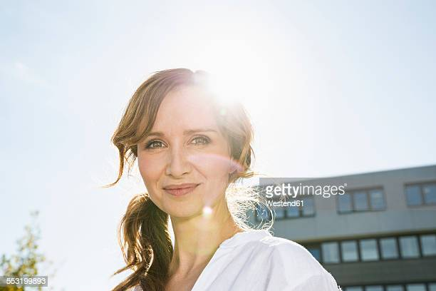 portrait of smiling businesswoman at backlight - gegenlicht stock-fotos und bilder