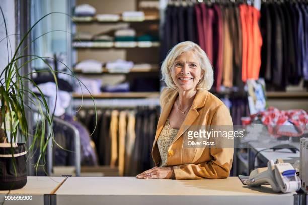 portrait of smiling businesswoman at counter in fashion store - werkneemster stockfoto's en -beelden