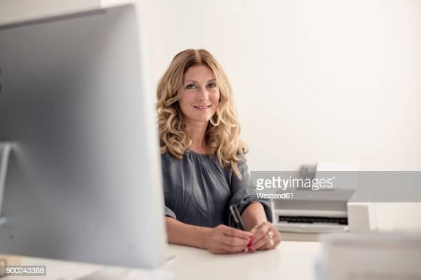 portrait of smiling businesswoman at desk in office - solo una donna matura foto e immagini stock