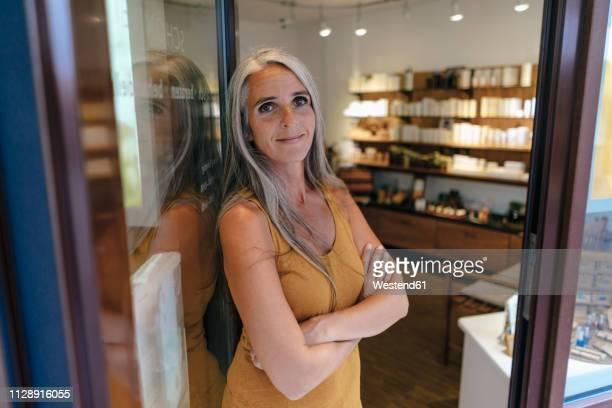 portrait of smiling businesswoman at entrance of her shop - natürlicher zustand stock-fotos und bilder
