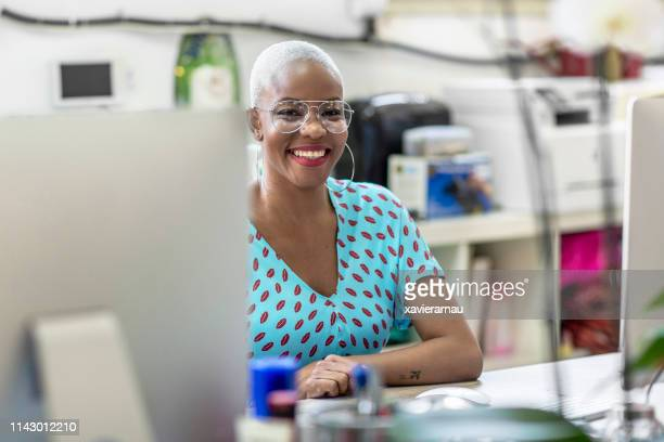 portrait of smiling businesswoman at office desk - fashion industry stock pictures, royalty-free photos & images