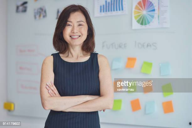 portrait of smiling businesswoman at office - sleeveless stock pictures, royalty-free photos & images