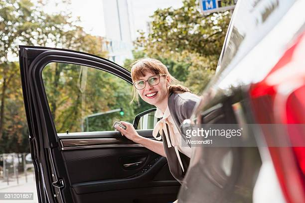 Portrait of smiling businesswoman getting off her car
