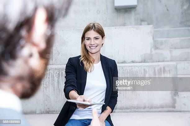 Portrait of smiling businesswoman giving digital tablet to her partner