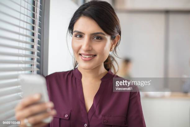 portrait of smiling businesswoman holding cell phone in office - blouse ストックフォトと画像