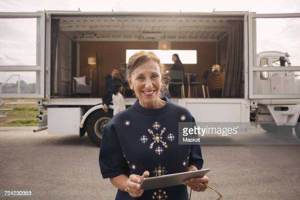 Portrait of smiling businesswoman holding digital tablet with colleagues and portable office truck in background