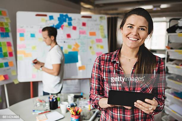 Portrait of smiling businesswoman holding digital tablet with colleague in background