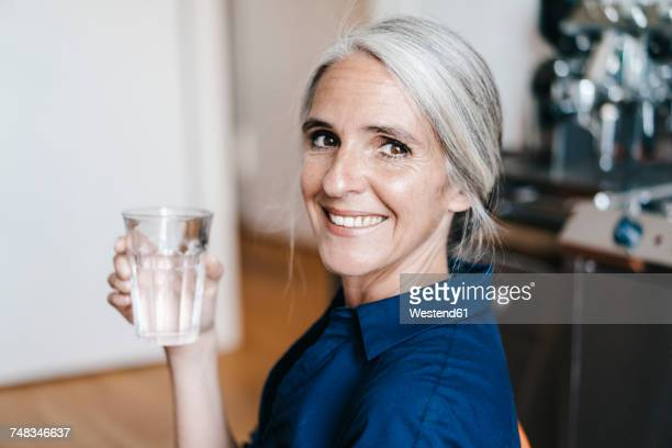 portrait of smiling businesswoman holding glass of water - drink water stock pictures, royalty-free photos & images