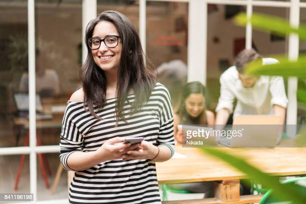 Portrait of smiling businesswoman holding mobile phone