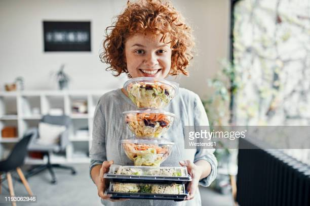 portrait of smiling businesswoman holding stack of takeaway food in office - lunch stock-fotos und bilder
