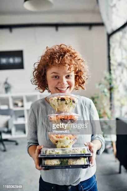 portrait of smiling businesswoman holding stack of takeaway food in office - aufwärmen stock-fotos und bilder
