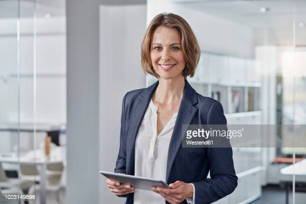 portrait of smiling businesswoman holding tablet in office - waist up stock pictures, royalty-free photos & images