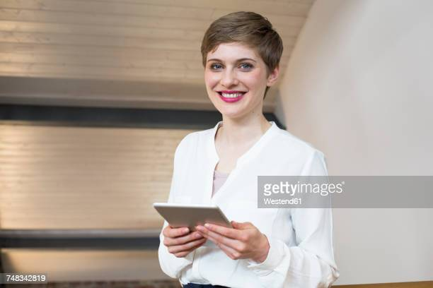 portrait of smiling businesswoman holding tablet - blouse ストックフォトと画像