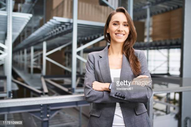 portrait of smiling businesswoman in a factory - grey blazer stock pictures, royalty-free photos & images