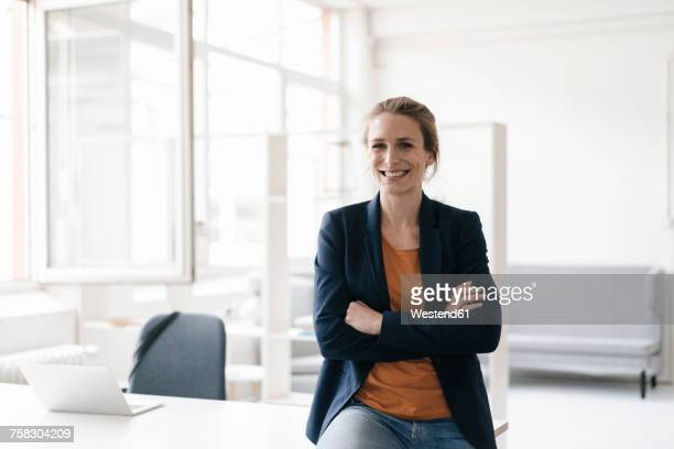 portrait of smiling businesswoman in a loft - weibliche angestellte stock-fotos und bilder