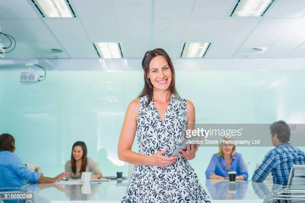 Portrait of smiling businesswoman in modern conference room