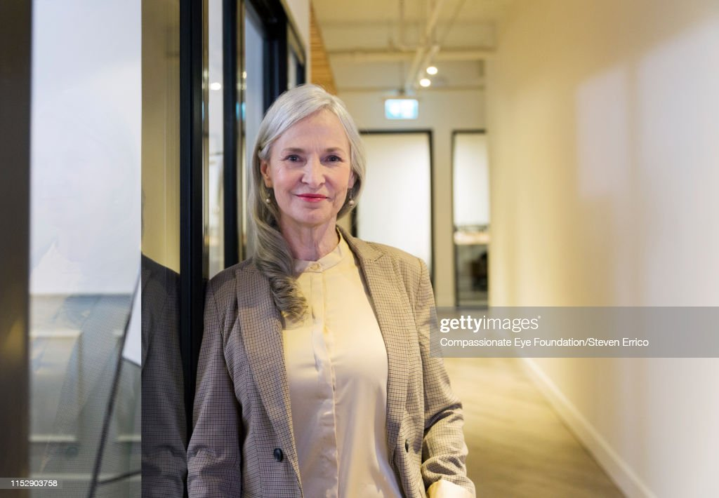 Portrait of smiling businesswoman in modern office : Stock Photo
