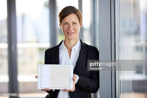 portrait of smiling businesswoman in office holding tablet showing ascending line graph - tuig mast stockfoto's en -beelden