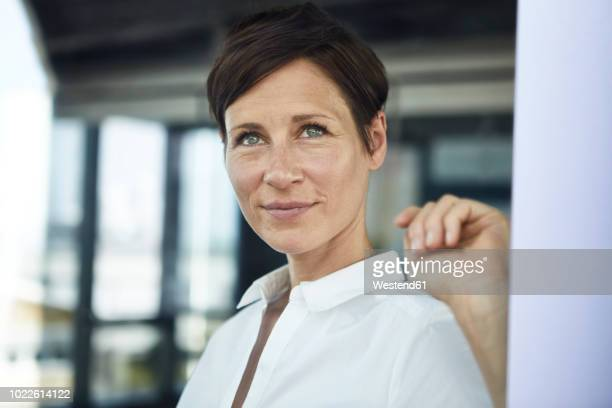 portrait of smiling businesswoman in office looking out of window - looking away stock pictures, royalty-free photos & images