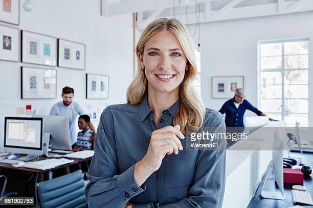 portrait of smiling businesswoman in office with staff in background - finance and economy stock pictures, royalty-free photos & images