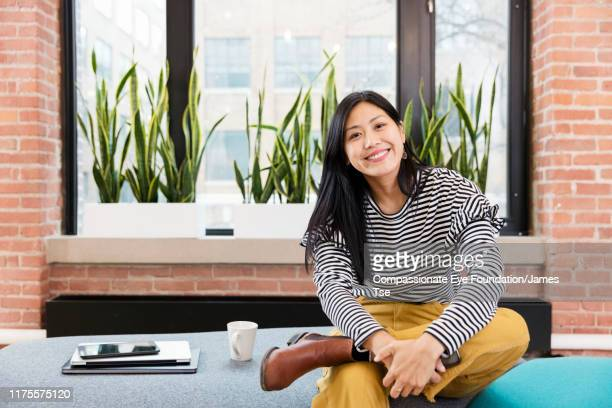 """portrait of smiling businesswoman in open plan office - """"compassionate eye"""" stock pictures, royalty-free photos & images"""