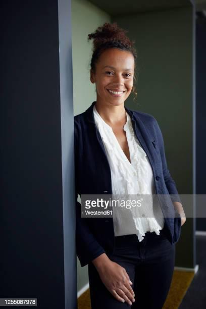 portrait of smiling businesswoman leaning at door case - chemisier photos et images de collection