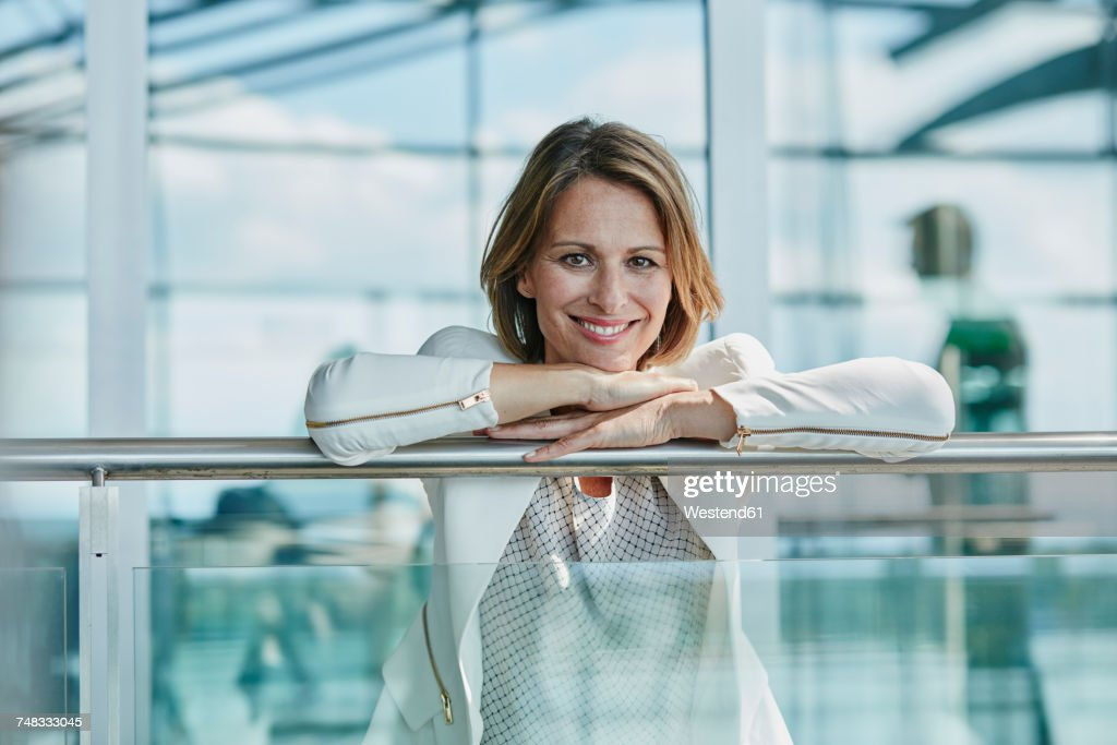 portrait of smiling businesswoman leaning on railing at the airport