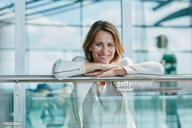 portrait of smiling businesswoman leaning on railing at the airport - garde corps photos et images de collection