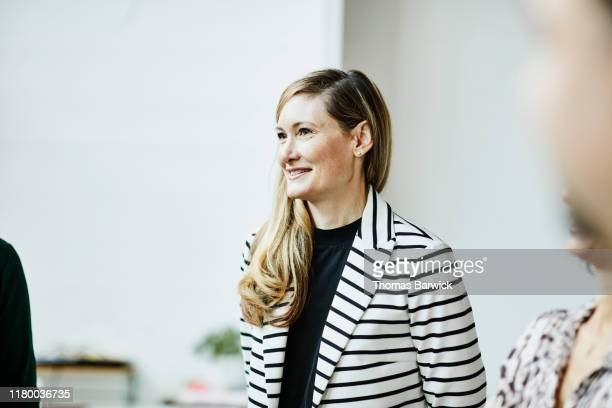 portrait of smiling businesswoman listening during meeting in office - striped blazer stock pictures, royalty-free photos & images