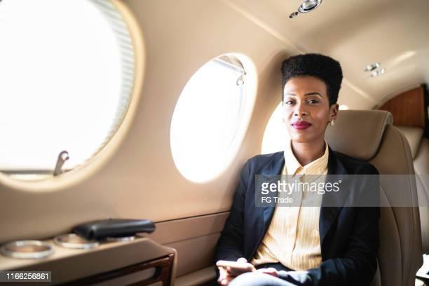企業のジェット機でカメラを見ている笑顔のビジネスウーマンの肖像 - 中南米 ストックフォトと画像