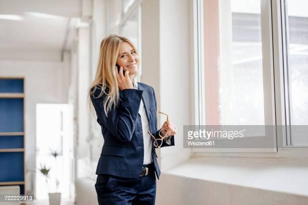 portrait of smiling businesswoman on cell phone in office - sakko stock-fotos und bilder