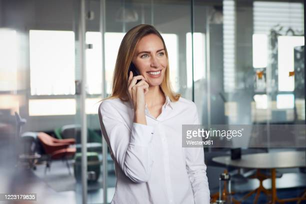 portrait of smiling businesswoman on the phone in office - blouse stock pictures, royalty-free photos & images