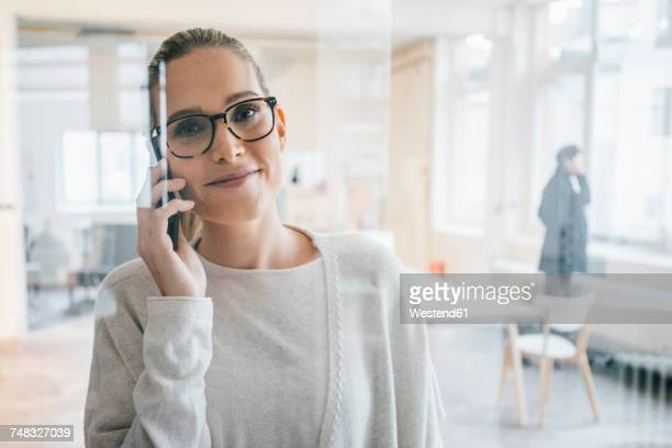 Portrait of smiling businesswoman on the phone in the office