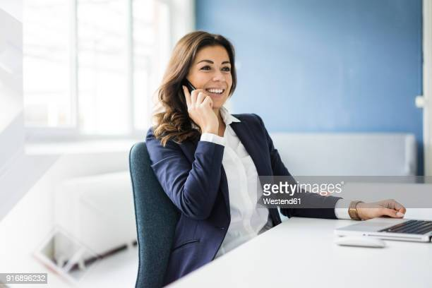 portrait of smiling businesswoman on the phone sitting at desk in an office - capelli castani foto e immagini stock