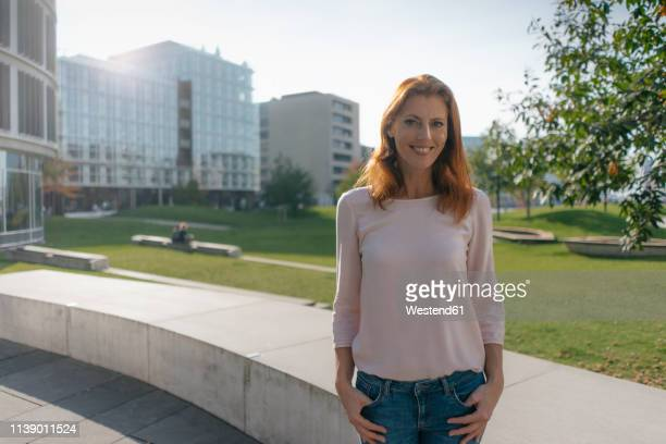portrait of smiling businesswoman outdoors in the city - one mature woman only stock-fotos und bilder