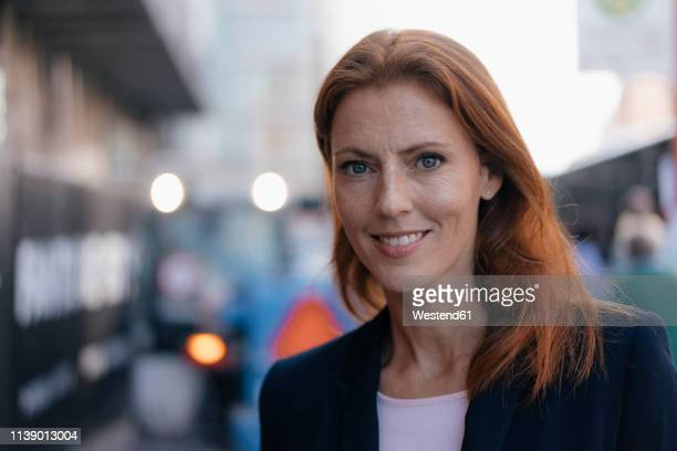 portrait of smiling businesswoman outdoors in the city - older redhead stock pictures, royalty-free photos & images