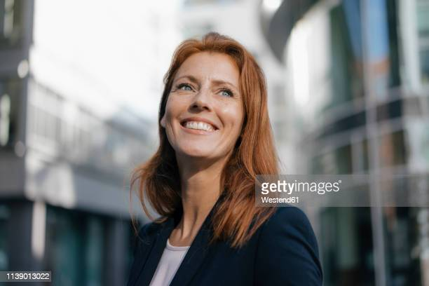 portrait of smiling businesswoman outdoors in the city - femme rousse photos et images de collection