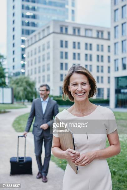 Portrait of smiling businesswoman outdoors with laptop and businessman in background