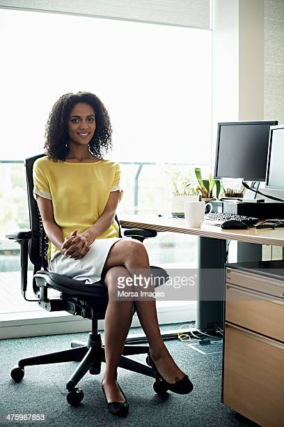 portrait of smiling businesswoman - cross legged stock pictures, royalty-free photos & images