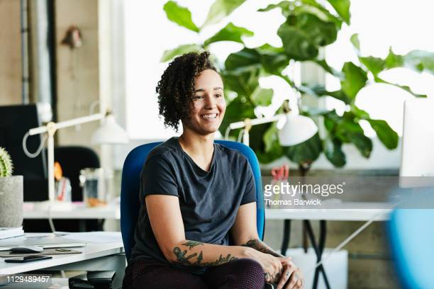 Portrait of smiling businesswoman seated at workstation in design office