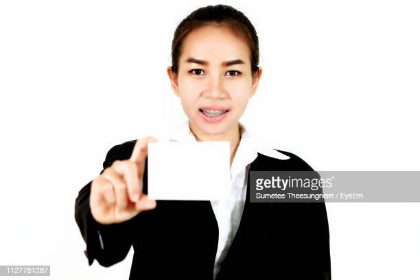 Portrait Of Smiling Businesswoman Showing Blank Card Against White Background