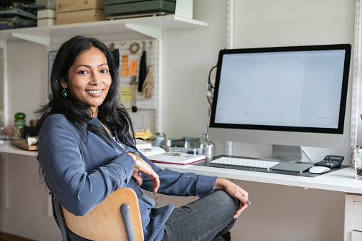 Portrait of smiling businesswoman sitting at desk in home office - gettyimageskorea