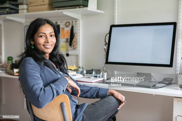 portrait of smiling businesswoman sitting at desk in home office - adults only stock pictures, royalty-free photos & images