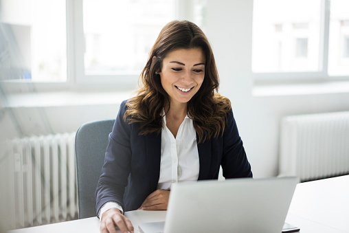 Portrait of smiling businesswoman sitting at desk in the office working on laptop - gettyimageskorea