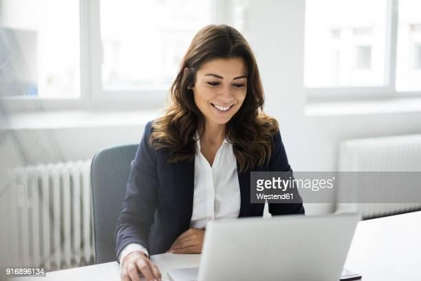 portrait of smiling businesswoman sitting at desk in the office working on laptop - geschäftsfrau stock-fotos und bilder