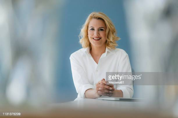 portrait of smiling businesswoman sitting at table - chemisier blanc photos et images de collection