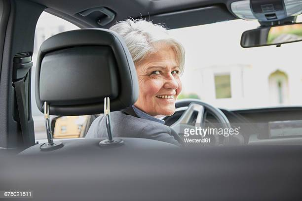 Portrait of smiling businesswoman sitting in a car