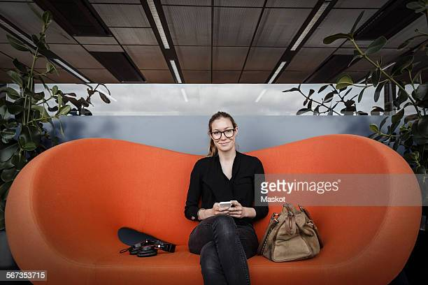 Portrait of smiling businesswoman sitting on orange couch in office