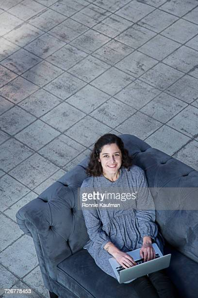 Portrait of smiling businesswoman sitting on sofa using laptop