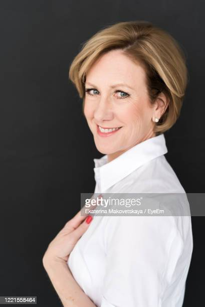 portrait of smiling businesswoman standing against black background - einzelne frau über 40 stock-fotos und bilder